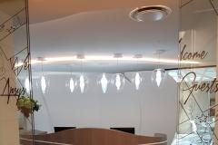 Banque d'accueil gainage tuiles en cuir blanc+ déco ceintures cuir blanc sur façade de comptoir